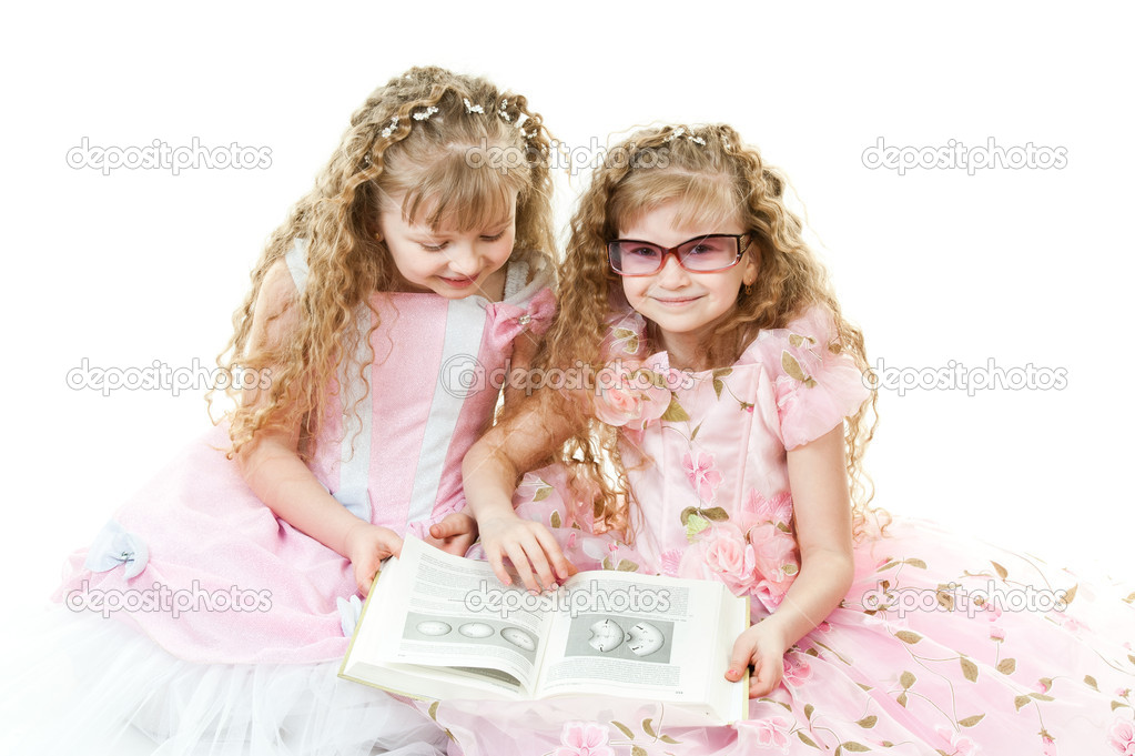 Two twin sisters in beautiful rose dresses reading a book isolated — Stock Photo #5395451