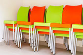 Colorful chairs for the visitors piled on each other and ranked — Stock Photo