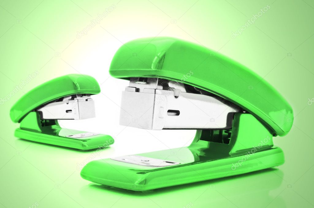 Close up of two  green office staplers isolated over pale green light effect — Stock Photo #5387825