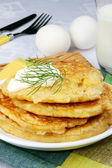Golden pancakes with sour cream — Stock Photo