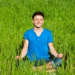 Young man meditation on green grass — Stock Photo