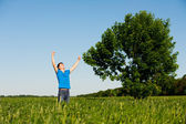 Happy man against tree and blue sky — Stock Photo
