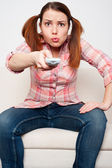 Woman sitting on sofa and watching tv — Stock Photo