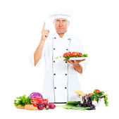 Serious chef holding plate with vegetables — Stock Photo