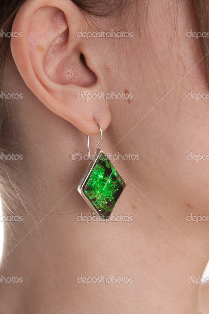 Amber earring on female ear. Closeup. Studio shot.  Stock Photo #6325393