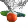 Tomato and cucumber under water — Stock Photo