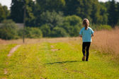 Child goes on a country road. — Stock Photo