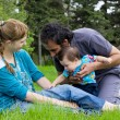 Happy family relaxing at the park - Stock Photo