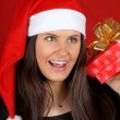Santa Claus girl shaking Christmas present — Stockfoto