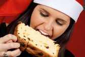 Santa Claus girl eating panettone — Stock Photo