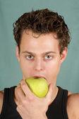 молодой человек кусает яблоко — Стоковое фото
