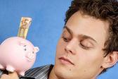 Jongeman met piggy bank — Stockfoto