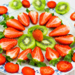 Fresh strawberries and kiwi fruit sliced on a plate — Stock Photo