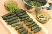 Cooking Turkish food stuffed grape leaves with rice and spices — Stock Photo