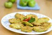 Sliced green tomatoes fried in soft dough with spices — Stock Photo