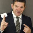 Business man handing a blank business card over gray  background — Stock Photo
