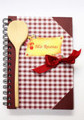 The book of recipes with a wooden spoon and a red bow. — Stock Photo