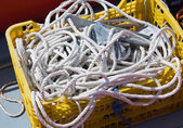Yellow plastic basket c white cords — Stock Photo