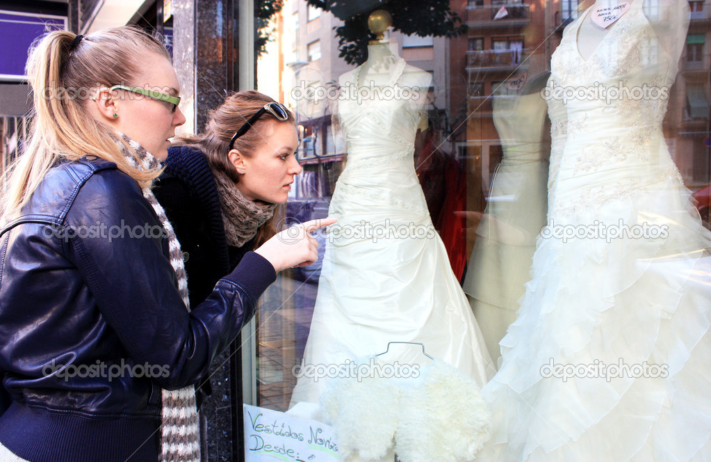 Two young girls are considering wedding dresses in a shop window. — Stock Photo #6089442