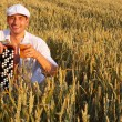Man with beer and  bayan in the wheaten field — Stock Photo