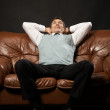Happy man on sofa - Stock Photo