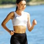 Sports girl runs near river — Stock Photo
