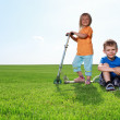 Two children in grass with skateboard — Stock Photo