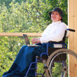 Sitting in wheelchair using laptop - Stock Photo