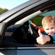 Boy sitting in car, smiling at the camera - Stock Photo