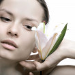 Young woman holding lily flower close to her face. — Stock Photo #6007999
