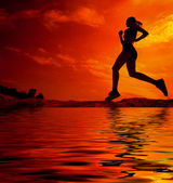 Female runner silhouette is mirrored below with a soft pastel sunset sky as backdrop — Stock Photo