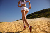Woman jogging on sand — Stock Photo