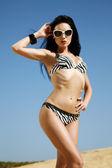 Bikini model in fashionable beachwear and sunglasses — Stock Photo