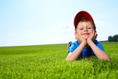 Smiling boy in grass — Stock Photo