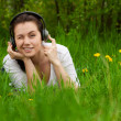 Winking girl with headphones lying on the grass — Stock Photo