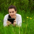 Smiling girl with ebook lying on the grass — Stock Photo #5603440