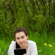 Girl with ebook lying on the grass — Stock Photo
