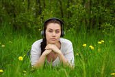 Girl with headphones lying in the grass ans looking streight — Stock Photo