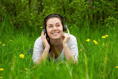 Laughting woman with headphones on the grass — Stock Photo
