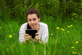 Smiling girl with ebook lying on the grass — Stock Photo