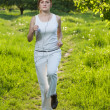 Young woman runing in a park and listen to music - Stock Photo