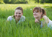 Happy sisters lying in grass — Stock Photo