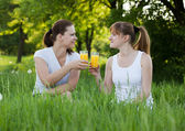 Sisters drinking orange juice in a park — Stock Photo