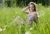 Happy girl sitting in a grass — Stock Photo
