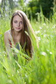 Young beautiful girl siting in the grass — Stock Photo