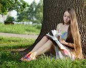 Teenager in a park with notebook — Stock Photo