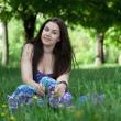 Stock Photo: Young smiling woman sitting in the grass