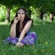 Stock Photo: Hippy with cigarette sitting in grass
