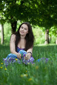 Young smiling woman sitting in the grass — Stock Photo