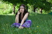 Hippy with cigarette sitting in the grass — Stock Photo